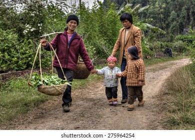 Yang Di village, Yangshuo, Guangxi, China - March 29, 2010: On country road in farmland is walking asian family, women and children, farmer carries on his shoulder a pole counterbalance to two baskets