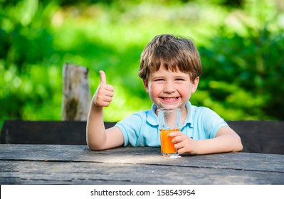 Yang little and cute boy pictured with glass of juice.