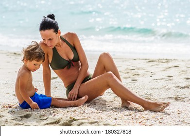 Yang mother and her son enjoy each other on the beach.