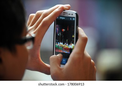 YANGON, BURMA - FEB 10: A temple-goer uses a smartphone to share a photo via Instagram at a Buddhist temple ceremony during festivities ushering in the Chinese New Year on Feb 10, 2013 in Yangon, Burma.