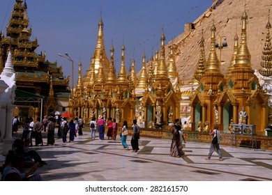 YANGON, BURMA - FEB 18, 2015 - Buddhist visitors walk along the wide platform of the Shwedagon Pagoda Yangon (Rangoon),  Myanmar (Burma)