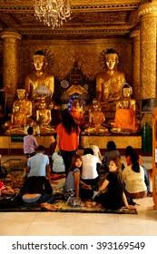 YANGON, BURMA - FEB 18, 2015 - Visitors at Buddhist temple in Shwedagon Pagoda Yangon (Rangoon),  Myanmar (Burma)