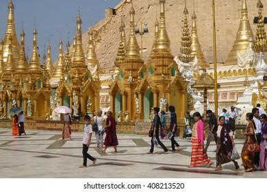 YANGON, BURMA - FEB 18, 2015 - Buddhist visitors walk along the wide platform of the Shwedagon Pagoda in Yangon (Rangoon),  Myanmar (Burma)
