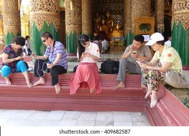 YANGON, BURMA - FEB 18, 2015 - Young Burmese  using cellphones in Shwedagon Pagoda,  Yangon (Rangoon),  Myanmar (Burma)