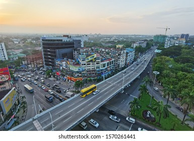 Yangon city, Myanmar 13 November 2019 ; The yellow bus on the bridge over the local square road with the clear traffic in Yangon, Myanmar. With high building tower and local house beside the road.