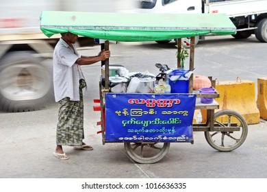 Yangon - December 29, 2017: A man is hauling his colorful food cart on main road of Yangon, Myanmar