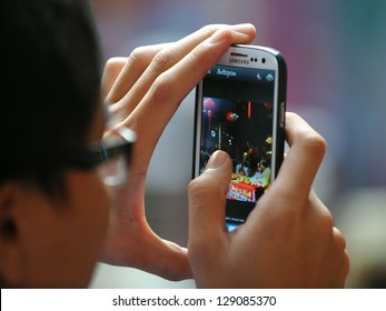 YANGON - FEB 10: A temple-goer uses a smartphone to share a photo via Instagram at a temple ceremony during festivities ushering in the Chinese new year of the snake on Feb 10, 2013 in Yangon, Burma.