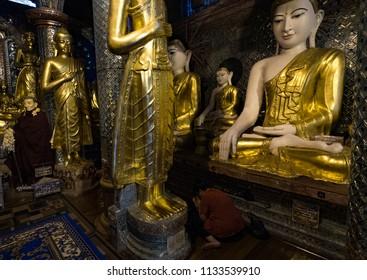 Yangon, Myanamr, Jun 2017: Woman prays amongst statues of Buddha, Shwedagon Temple, Yangon, Maynmar
