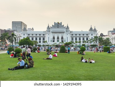 Yangon, Myanmar - 16.05.2019: People sitting on grass in Maha Bandula park in front of Yangon City Hall building at Burma.