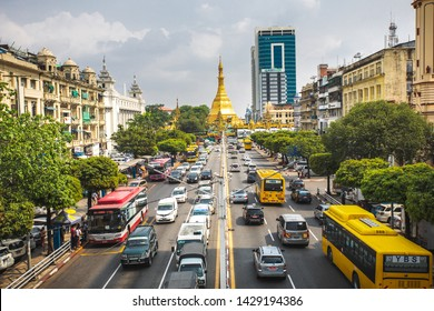 Yangon, Myanmar - 16.05.2019: View on the Yangon city downtown with traffic and golden stupa of Sule Pagoda. Sula Pagoda is Landmark od Yangon and Burma.