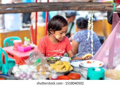 Yangon, Myanmar - 20.05.2019: Young burmese boy preparing traditional street food at Yangon. Children in trhird world.