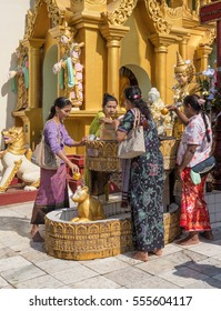 Yangon, Myanmar - 25 December 2016 - People pour water on buddha at the Shwedagon Pagoda in Yangon, Myanmar.