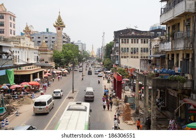 Yangon, Myanmar - April 6, 2014: View from a pedestrian overpass on Sule Pagoda Road of traffic, people, and buildings in downtown Yangon. The historic Sule Pagoda is at the end of the street.