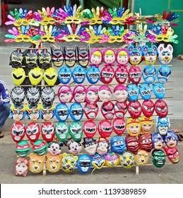 Yangon, Myanmar - December 29, 2017: Colorful heroes masks selling beside road, street market in Yangon or formerly known as Rangoon.