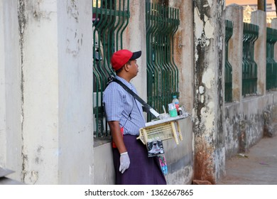 Yangon, Myanmar, Feb 22, 2019 : Myanmese male street vendor selling betel quids, it is a areca nuts, lime and tobacco wrapped in a betel leaf for chew, beside the walkway in Yangon.