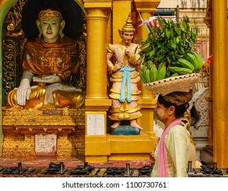 Yangon, Myanmar - Feb 26, 2016. A woman with fruit offerings walking at Shwedagon Pagoda in Yangon, Myanmar.