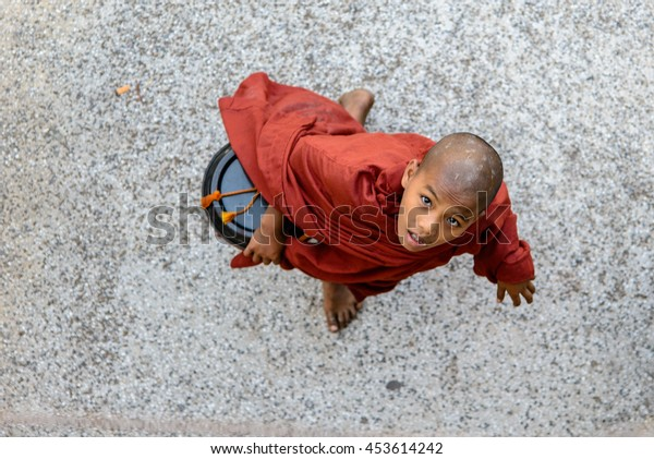 YANGON, MYANMAR - FEBRUARY 07, 2014: young monk in red robe