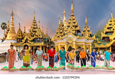 YANGON, MYANMAR - FEBRUARY 12, 2019: Women sweep the marble floor of the Shwedagon Pagoda in Yangon, Myanmar