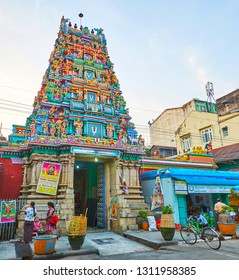 YANGON, MYANMAR - FEBRUARY 15, 2018: The scenic gopuram tower above the entrance to historic Sri Varatha Raja Perumal Temple, decorated with sculptures of Hindu deities, on February 15 in Yangon.