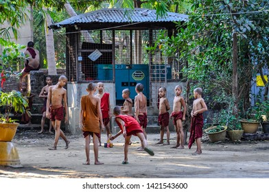 YANGON, MYANMAR - FEBRUARY 22, 2013: Buddhist boys playing in the courtyard in the colonial city of Yangon, Myanmar