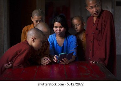 Yangon, Myanmar - February 27 2017: Many Buddhist novices have crowded around a woman and excited to watch something from her mobile phone.