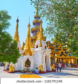 YANGON, MYANMAR - FEBRUARY 27, 2018: The golden stupas of Shwedagon Zedi Daw with ringing hti umbrellas and tall pyatthat (multistaged) roof on the background, on February 27 in Yangon.