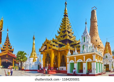 YANGON, MYANMAR - FEBRUARY 27, 2018: The shrines and Image Houses along Northern alley of Shwedagon Zedi Daw with Naungdawgyi Pagoda, covered in restauration constructions, on February 27 in Yangon