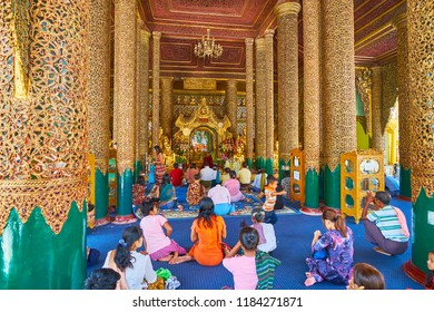 YANGON, MYANMAR - FEBRUARY 27, 2018: The crowded prayer hall of Gautama Buddha Image House of Shwedagon Zedi Daw, decorated with intricate carved patterns and mirror inlay, on February 27 in Yangon