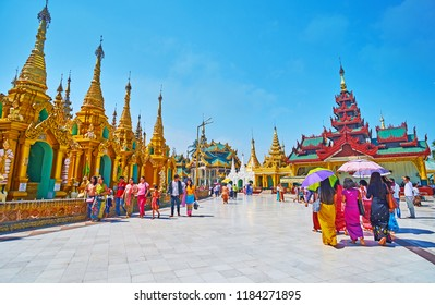 YANGON, MYANMAR - FEBRUARY 27, 2018: Tourists and pilgrims walk around the Shwedagon Zedi Daw with line of outer golden stupas on platform and the Image Houses on background, on February 27 in Yangon