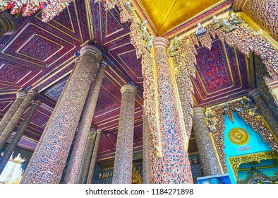 YANGON, MYANMAR - FEBRUARY 27, 2018: The intricate carved pattern with mirror inlay on columns and ceiling panels of Gautama Buddha Image House in, Shwedagon Zedi Daw, on February 27 in Yangon