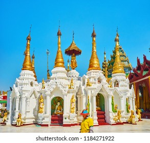 YANGON, MYANMAR - FEBRUARY 27, 2018: The carved stucco shrines with golden stupas and ornate hti umbrellas at the Point of Victory (Aspicious Ground) of Shwedagon Zedi Daw, on February 27 in Yangon