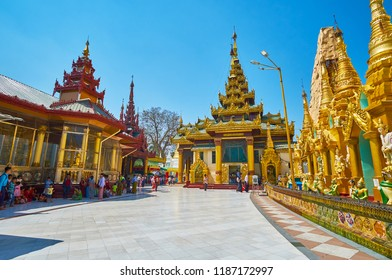 YANGON, MYANMAR - FEBRUARY 27, 2018:  The building of Curio Museum (from the left) and Konagomana Buddha Image House (in the middle) in Shwedagon Zedi Daw, on February 27 in Yangon