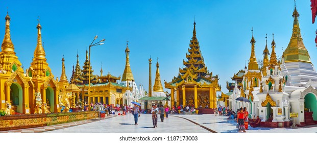 YANGON, MYANMAR - FEBRUARY 27, 2018:  Panorama of Shwedagon Zedi Daw with pilgrims in circle alley, bright golden stupas and the image house with intricate pyatthat roof, on February 27 in Yangon