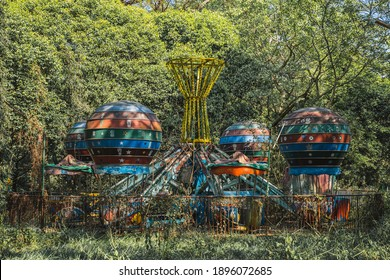 YANGON, MYANMAR - JANUARY 10, 2020: A multi-colored fairground ride sits amongst foliage in an abandoned theme park in central Yangon, Myanmar.