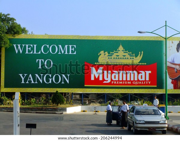 """YANGON, MYANMAR - JANUARY 11: Unidentified men stand by """"Welcome to Yangon sign"""" on January 11, 2012 in Yangon, Myanmar. Yangon is the largest city and the most important commercial center in Myanmar."""