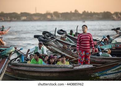 YANGON, MYANMAR - JANUARY 3, 2016: Unidentified men traveling by a jetty on the Yangon River in Yangon , Myanmar on January 3, 2016