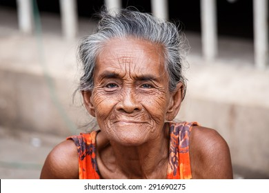YANGON, MYANMAR - JUNE 12 2015: Older lady sits on the street on one of the hottest recorded days before monsoon season in Yangon, Myanmar.