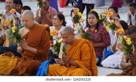 Yangon / Myanmar - March 2017: Monk in orange robe praying in the Shwedagon Pagoda.