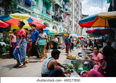 YANGON, MYANMAR - MAY 31, 2015: People transit in the street markets of the city of Yangon