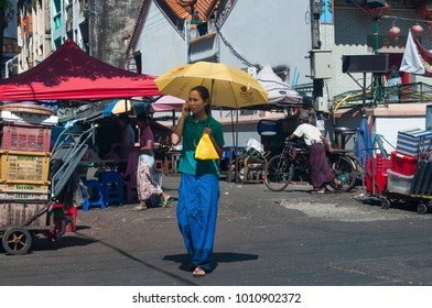 YANGON, MYANMAR - NOVEMBER, 2016: Girl walking in the streets of Yangon. She uses an umbrella to protect from the sun.