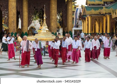 YANGON, MYANMAR - NOVEMBER 26, 2016: Ordination ceremony at the sunset  in the Shwedagon pagoda with monks walking around the pagoda and carrying sacred items