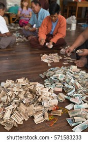 YANGON, MYANMAR - NOVEMBER 27, 2016: a man is counting the money of the generous offers to the Myanmar monks