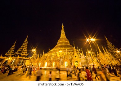 YANGON, MYANMAR - NOVEMBER 27, 2016: people walking and praying in the night  at the Shwedagon pagoda the most famous pagoda of southest Asia.