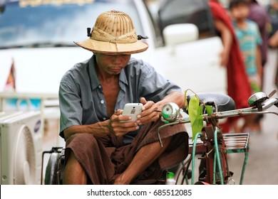 Yangon,Myanmar October 20,2016 A man look at him mobile phone in Yangon Myanmar, selective focus.