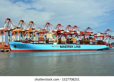Yangshan, Shanghai / China - September 24 2019: Maersk Line owned large cargo container ship in the port of Yangshan, gantry cranes during cargo operations, loading and unloading containers.