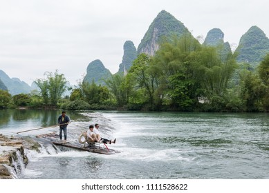 YANGSHUO, CHINA - APRIL 24, 2017 - Tourists and their guide float down the Yulong River on a bamboo raft. The Yulong River is located in a region of China famous for its limestone karsts.