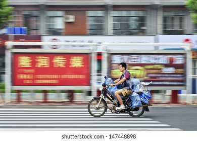 """YANTAI-CHINA-JULY 22. Man transports water tanks. Outlook on quality of China's water sources is """"far from optimistic,"""" according to the Ministry of Environmental Protection. Yantai, July 22, 2013."""