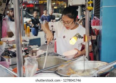 Yaowarat, Bangkok, Thailand - December circa, 2018: Female street vendor at Yaowarat food street market selling a serve of Braised Fish Maw in Red Gravy, popular dish from Thai - Chinese cuisine.