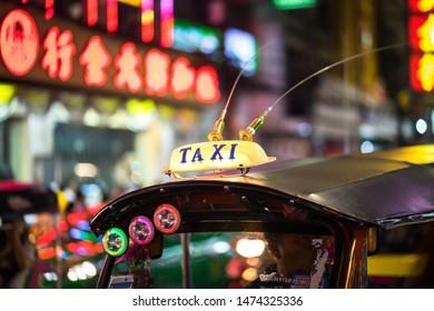 Yaowarat road, Bangkok / Thailand - July 2019 : Tuk Tuk (Taxi) is parking and waiting for passenger at Yaowarat famous China town of Thailand. Close up at Taxi light sign.