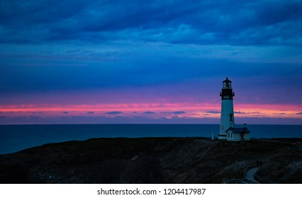 The Yaquina Head Lighthouse with a blue and pink sunset at Newport, Oregon.